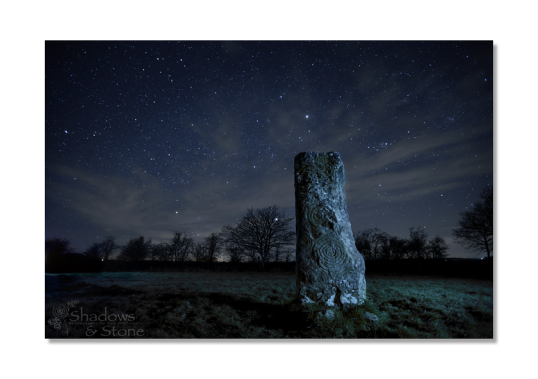 The night sky above the spiral covered solitary remainder of a destroyed passage tomb.