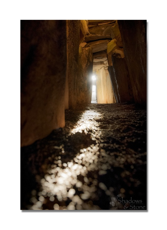 Winter Solstice sunrise shines through the roofbox above the door of Newgrange and along the passage floor